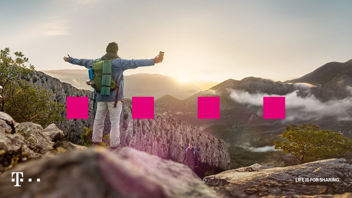 Hiker standing on cliff with cellphone in hand and Deutsche Telekom blocks - photo - 10th May 2019
