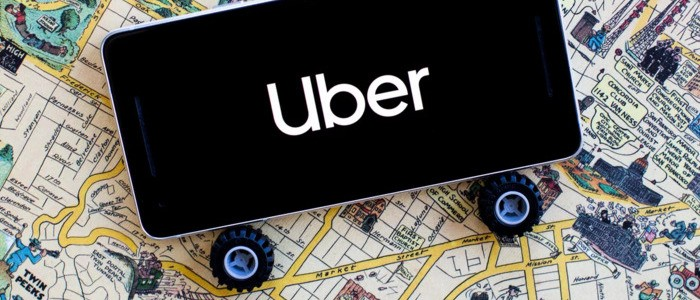 Mobile phone on toy wheels with Uber logo on, 'riding' on a map background - photo - 11th May 2020